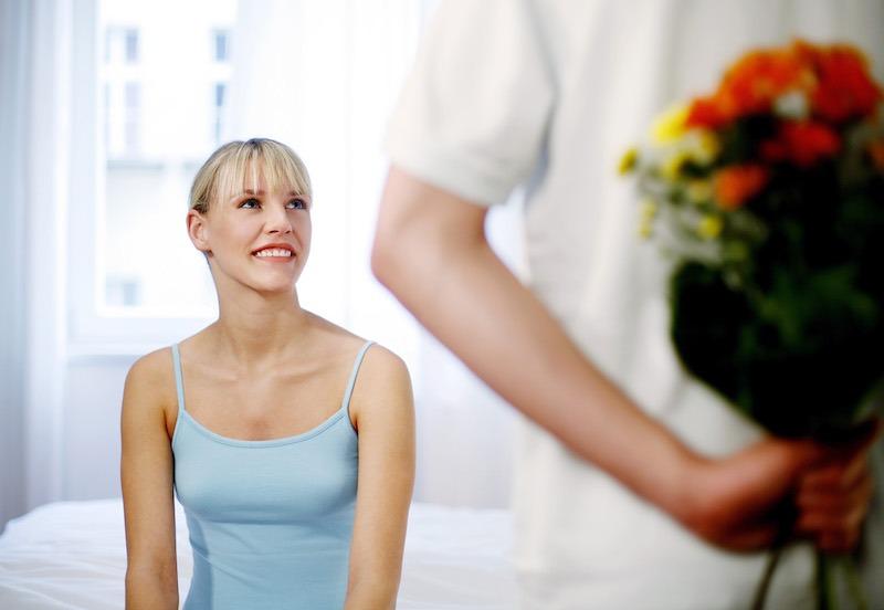 Homme offrant des fleurs à sa femme