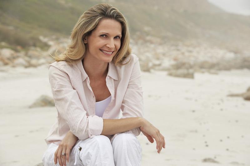 Femme souriante assise à la plage